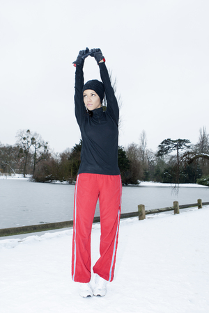 Runner stretching in snowy field LANG_EVOIMAGES