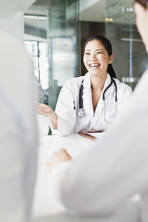 Doctor talking to colleagues in meeting