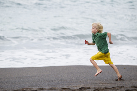 whimsy: Boy running on beach LANG_EVOIMAGES