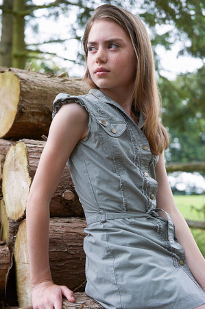 Teenage girl leaning on logs in  forest LANG_EVOIMAGES