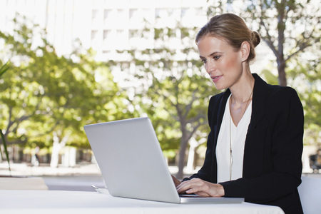 technology: Businesswoman using laptop outdoors