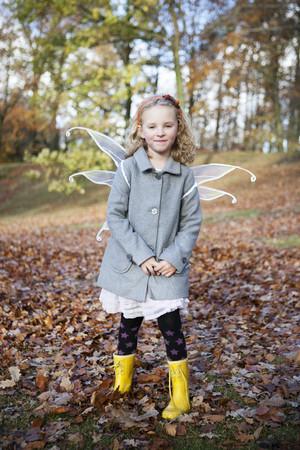 Girl wearing fairy wings in park