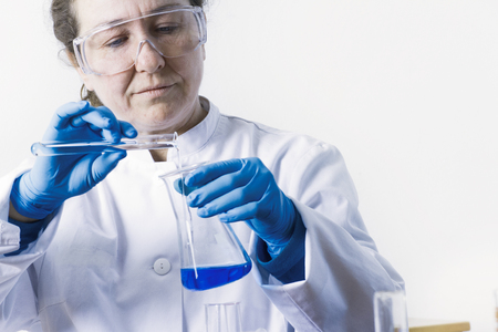 adds: Scientist pouring liquid into beaker