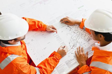 defended: Businessmen reading blueprints