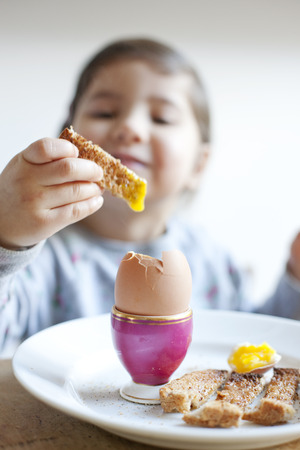 four objects: Girl dipping toast into egg at breakfast