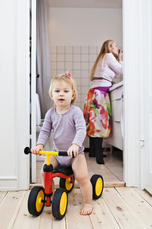 hard: Toddler girl playing on tricycle,mother in background