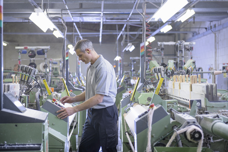 grays: Worker using loom in textile mill