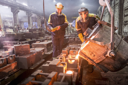 maneuvering: Workers pouring molten metal in foundry LANG_EVOIMAGES