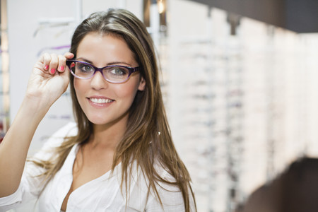shopper: Woman trying on glasses in store