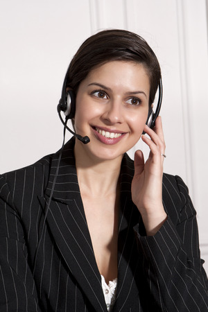 advice: Businesswoman talking on headset LANG_EVOIMAGES