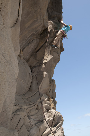 ascends: Rock climber scaling jagged cliff