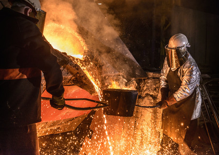 handlers: Worker pouring molten metal in foundry
