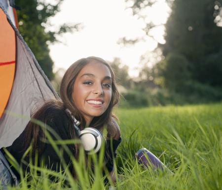 Teenage girl in headphones at campsite
