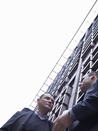 agrees: Businessmen talking on city street LANG_EVOIMAGES