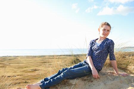 Teenage girl sitting on beach