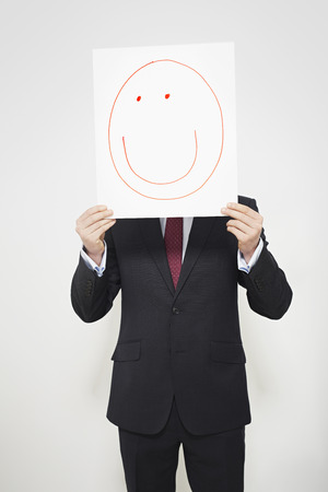 concealing: Businessman holding happy face over his face LANG_EVOIMAGES