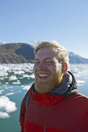 Man laughing by glacial lake