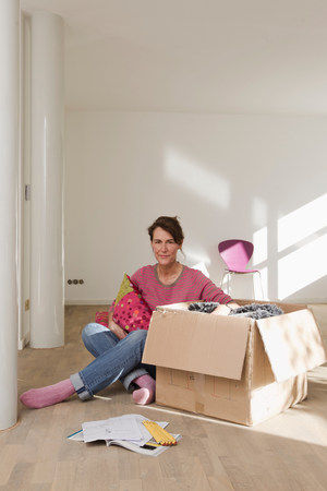 new age: Woman sitting on wooden floor unpacking cardboard box