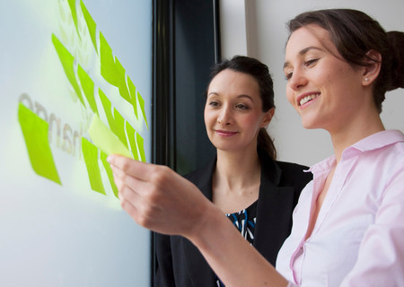 Female colleagues sticking adhesive notes on glass LANG_EVOIMAGES