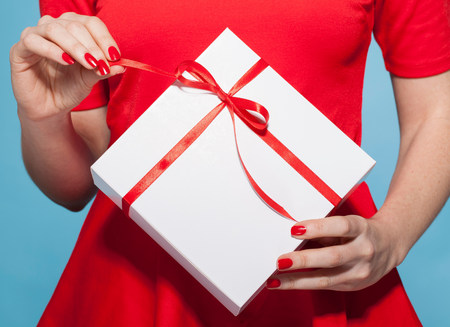 Woman opening white gift box with red bow,mid section