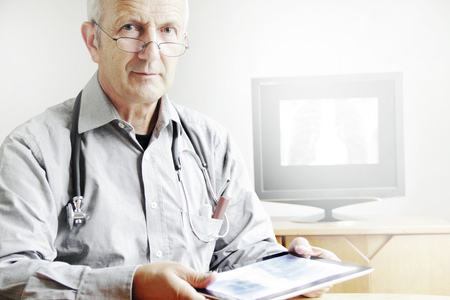 Doctor using tablet computer in office