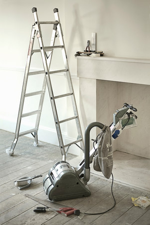 Ladders and sander by fireplace of new home