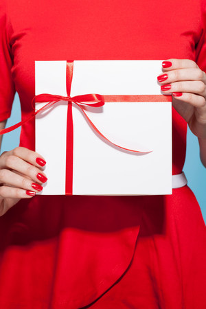 35 to 40 year olds: Woman holding white gift box with red bow,mid section LANG_EVOIMAGES
