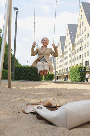 Senior woman on playground swing