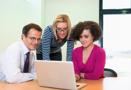 assured: Three colleagues working on laptop in office LANG_EVOIMAGES