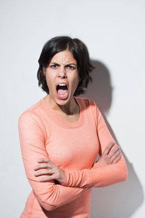 enraged: Portrait of young female shouting LANG_EVOIMAGES