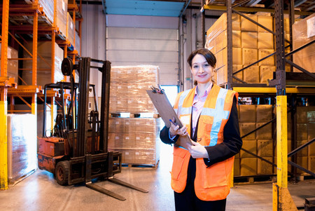 looking at viewer: Female supervisor in warehouse