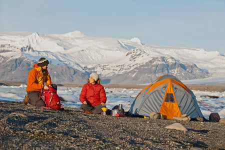 Couple by tent at glacier lake,Jokulsa Loni,Iceland