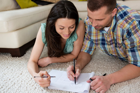 parlours: Mid adult couple lying on floor sketching house plans LANG_EVOIMAGES