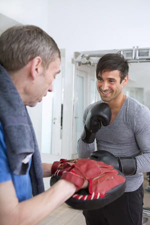 retiring: Boxer practicing with trainer in gym LANG_EVOIMAGES