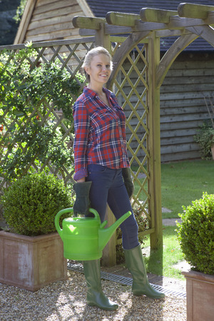 Woman carrying watering can in garden