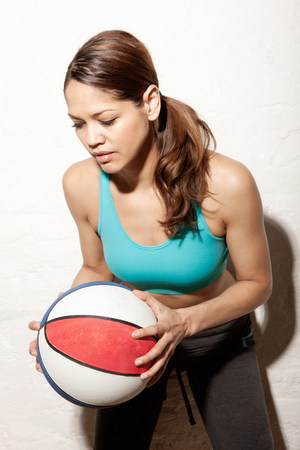 athleticism: Young woman holding basketball LANG_EVOIMAGES