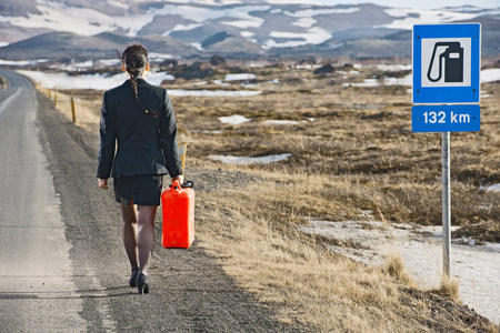 first day: Woman walking down road carrying petrol can