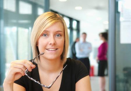 通信: Blonde woman holding glasses with colleagues in background