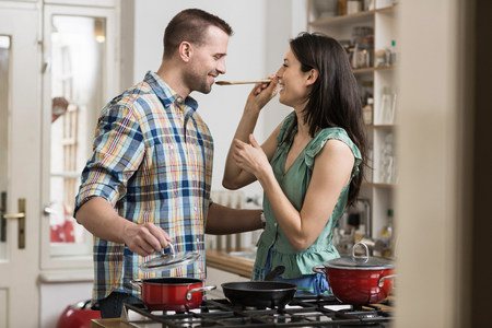 close up food: Mid adult couple cooking dinner,tasting