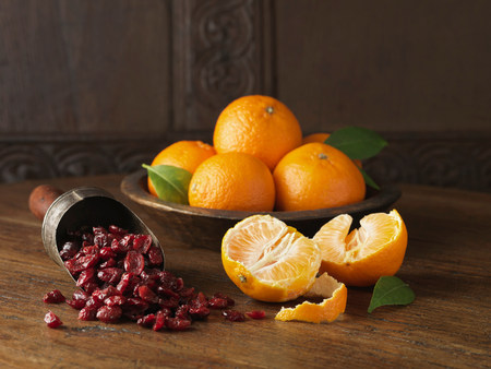 clementines: Recipe ingredients for dry cured gammon with clementines and cranberries. Whole and halved clementines with scoop of cranberries
