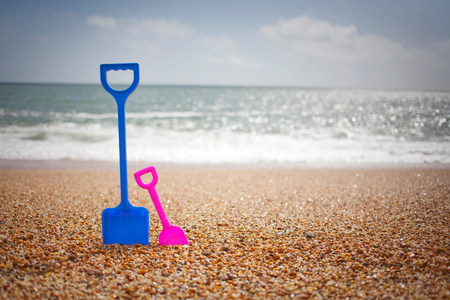 oversized: Blue and pink spades standing in sand at beach