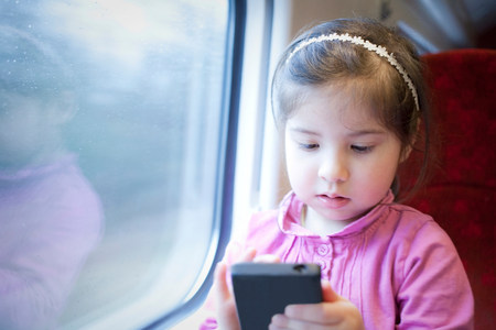 alice band: Little girl on train,playing game on smartphone