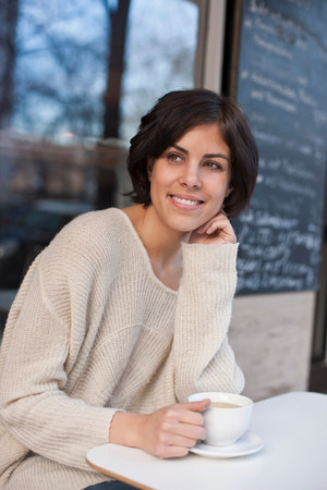 Portrait of woman outside cafe with coffee