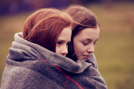 Girls wrapped in a blanket outdoors LANG_EVOIMAGES