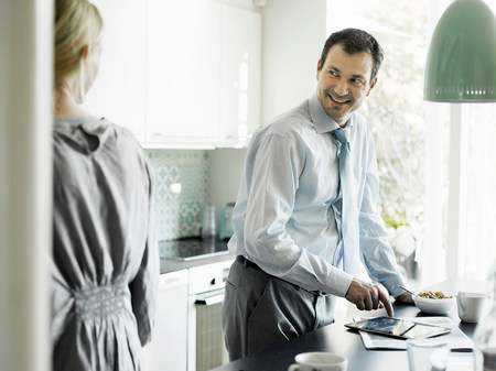electronic organiser: Mature businessman using tablet and smiling in kitchen