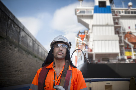 proudly: Worker standing on tug boat