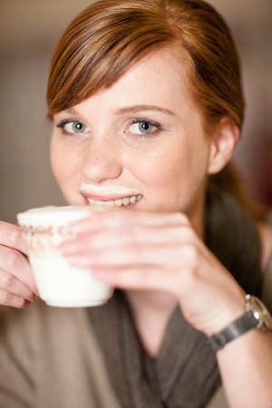 sipping: Smiling woman with milk mustache LANG_EVOIMAGES