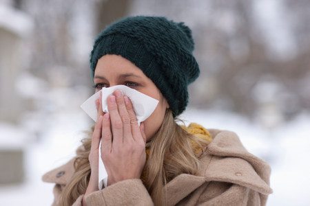 unhealthiness: Woman in hat blowing nose LANG_EVOIMAGES