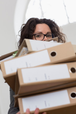 35 to 40 year olds: Businesswoman obscured by pile of folders