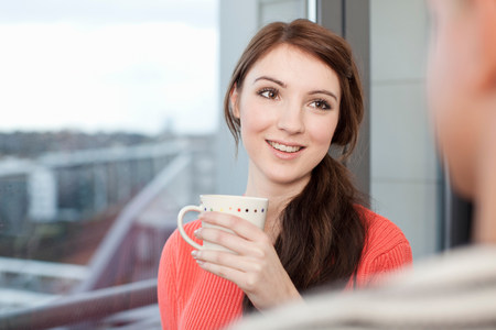 Young woman with coffee cup by window